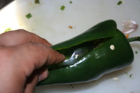 Take a spoon and gently remove the seeds and ribs from inside the pepper. The first one or two may take you a minute, but you should get the hang of it. Be thorough, poblanos are spicier than I thought they were.